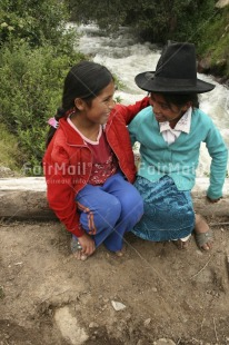Fair Trade Photo Activity, Artistique, Blue, Clothing, Colour image, Culture, Embracing, Emotions, Friendship, Happiness, Hat, Multi-coloured, Outdoor, People, Peru, Portrait fullbody, Red, River, Rural, Sitting, Smiling, South America, Together, Trust, Two children, Two girls, Vertical, Water