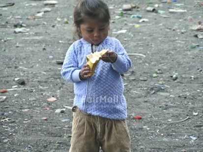 Fair Trade Photo Activity, Banana, Casual clothing, Child labour, Clothing, Colour image, Day, Eating, Food and alimentation, Fruits, Garbage, Garbage belt, Health, Horizontal, Hygiene, Looking away, One girl, Outdoor, People, Peru, Portrait fullbody, Recycle, Safety, Sanitation, South America