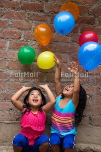 Fair Trade Photo Activity, Balloon, Colour image, Cooperation, Emotions, Friendship, Happiness, People, Peru, Playing, Smiling, South America, Throwing, Twin, Two girls, Vertical