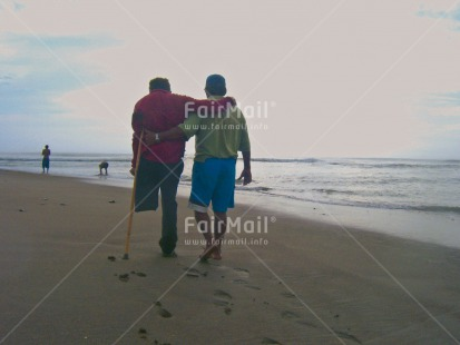 Fair Trade Photo Activity, Beach, Care, Colour image, Cooperation, Day, Friendship, Handicapped, Helping, Horizontal, Outdoor, People, Peru, Sea, Sickness, South America, Together, Two men, Walking