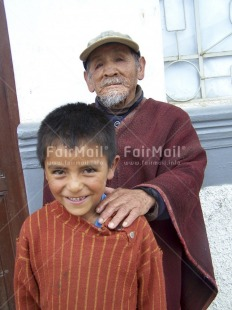 Fair Trade Photo Activity, Care, Clothing, Colour image, Dailylife, Family, Looking at camera, Multi-coloured, Old age, One boy, One child, One man, Outdoor, People, Peru, Poncho, Portrait halfbody, South America, Together, Traditional clothing, Vertical, Young