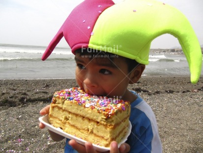 Fair Trade Photo Activity, Beach, Birthday, Cake, Clothing, Colour image, Colourful, Congratulations, Eating, Food and alimentation, Green, Hat, Horizontal, Looking away, One boy, Outdoor, Party, People, Peru, Pink, Portrait halfbody, Sand, Sea, South America