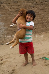 Fair Trade Photo Activity, Animals, Colour image, Dog, Emotions, Happiness, One boy, One child, Outdoor, People, Peru, Playing, South America, Vertical
