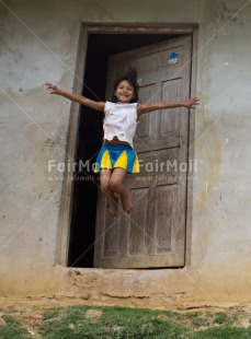 Fair Trade Photo Activity, Colour image, Door, Emotions, Happiness, House, Jumping, Looking at camera, One girl, People, Peru, Rural, Smiling, South America, Vertical