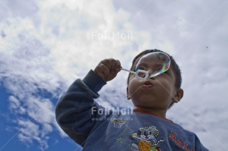 Fair Trade Photo Activity, Casual clothing, Clothing, Clouds, Colour image, Day, Horizontal, Looking away, One boy, Outdoor, People, Peru, Playing, Portrait halfbody, Rural, Seasons, Sky, Soapbubble, South America, Summer, Young