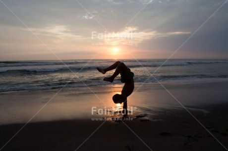 Fair Trade Photo 10-15_years, Activity, Backlit, Beach, Colour image, Doing handstand, Evening, Horizontal, One boy, Outdoor, People, Peru, Sea, Silhouette, South America, Sunset, Water, Yoga