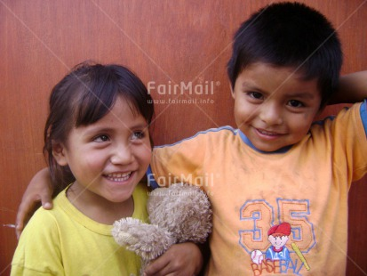 Fair Trade Photo Activity, Brother, Care, Casual clothing, Clothing, Colour image, Cute, Day, Family, Horizontal, Looking at camera, One boy, One girl, Outdoor, People, Peru, Portrait halfbody, Sister, Smiling, South America, Teddybear, Together, Two children, Warmth