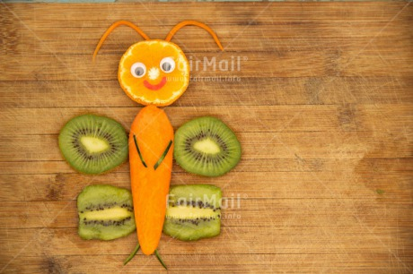 Fair Trade Photo Butterfly, Carrot, Colour image, Creativity, Food and alimentation, Fruits, Horizontal, Kiwi, Orange, Peru, Seasons, South America, Spring, Summer, Table, Wood