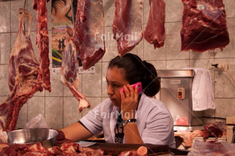 Fair Trade Photo 25-30_years, Activity, Calling, Colour image, Day, Entrepreneurship, Horizontal, Indoor, Latin, Looking away, Market, Meat, Mobilephone, One woman, People, Peru, Portrait halfbody, Selling, South America